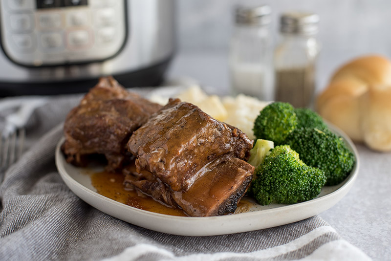 Bone-in pressure cooker Short Ribs plated with broccoli and mashed potatoes in front of an Instant Pot.