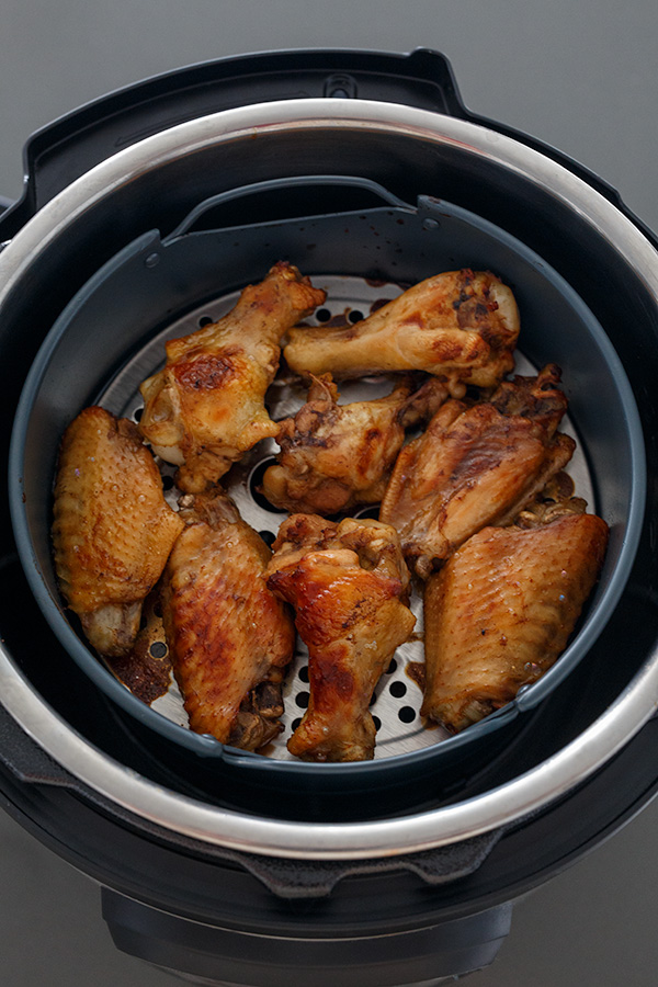 Teriyaki chicken wings browned up in an air fryer basket.