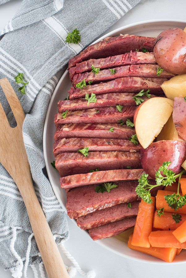Close up overhead of Instant Pot Corned Beef and Cabbage for St. Patrick's Day on a whtie serving platter with a white and grey linen napkin.