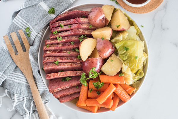Landscape overhead of Pressure Cooker Corned Beef and Cabbage on a white circular serving dish with a wooden spoon resting on a grey and white linen napkin.