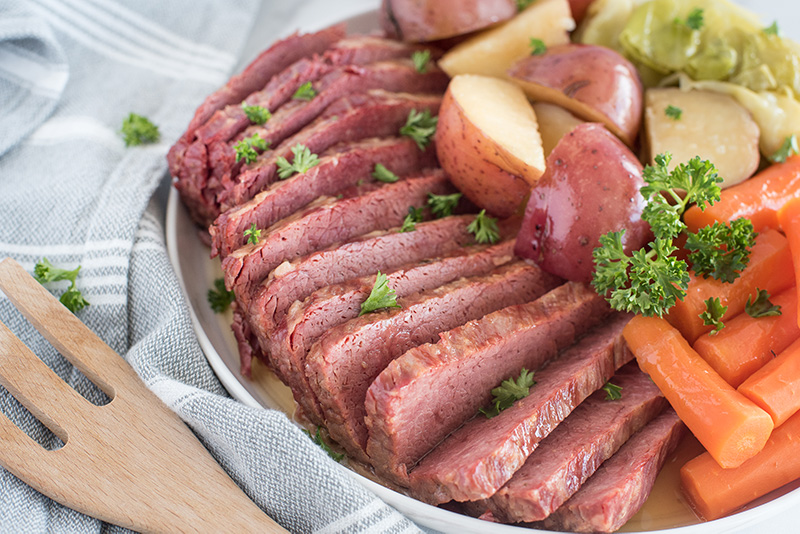 45 degree shot of thin slices of Instant Pot corned beef served with tender carrots, white potatoes, and cabbage, garnished with fresh parsley on a round white serving dish
