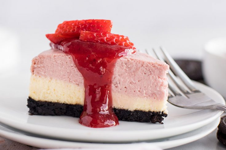 Close up of a layered strawberry cheesecake, cooked in an Instant Pot pressure cooker, garnished with a drizzle of strawberry sauce and fresh strawberries