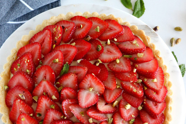 Del's Cooking Twist's Fresh Strawberry Tart with the strawberries sliced thin and spread out beautifully in overlapping circles across the top of the tart