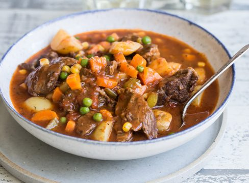 A bowl of Pressure Cooker Beef Stew with chunky potatoes, carrots, and peas in a bowl with a spoon.