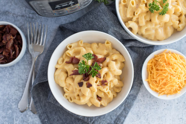 Over head of a bowl of creamy Instant Pot mac and cheese topped with crumbled bacon and fresh parsley with a bowl of shredded cheddar cheese and more bacon for topping on a grey background.