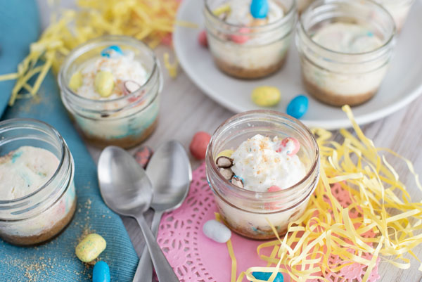 Individual Robin Egg Cheesecakes flavored with Whoppers Robin Eggs for Easter with Easter colored decorations and metal spoons