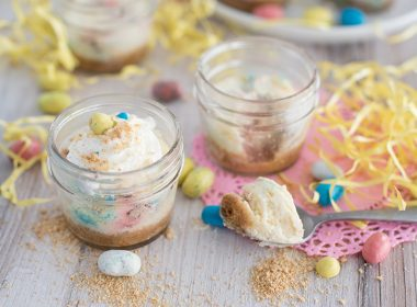Side view of two mini pressure cooker Robin Egg's Cheesecake made in mini glass mason jars with Whoppers Robin Eggs on a white wooden table decorated for Easter with an Instant Pot in the background.