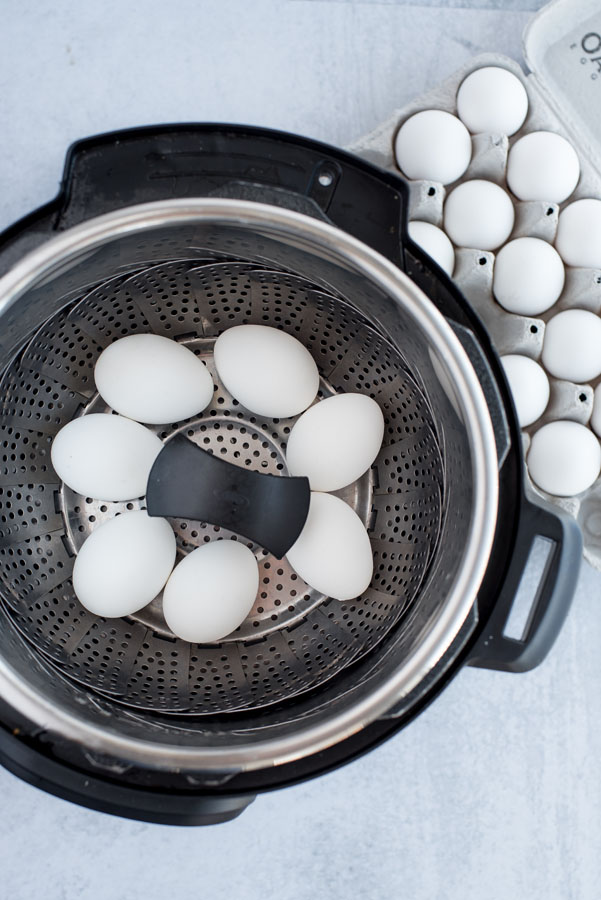 Overhead of An Instant Pot with a steamer basket inside with seven white eggs ready to be hard-boiled with a carton of eggs nearby.