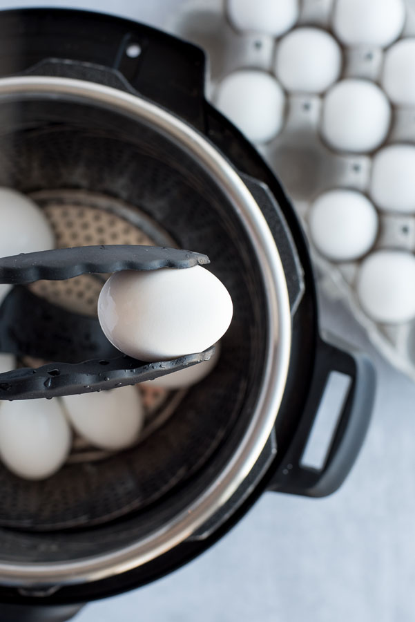 Close up of a white hard-boiled egg coming out of an Instant Pot with black and silver tongs.