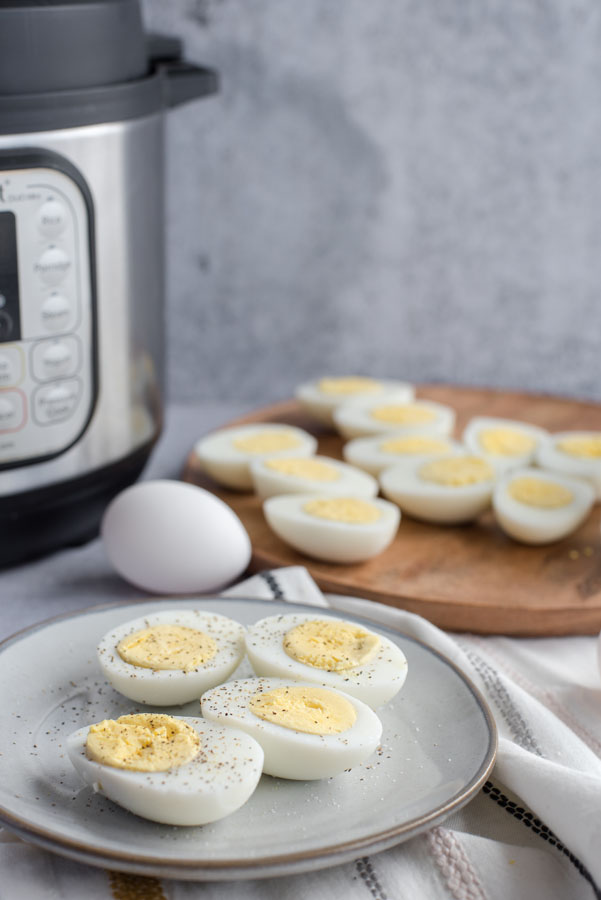 Side view of a grey ceramic plate with four halves of hard-cooked eggs with an Instant Pot and a large wooden tray of eggs in the background.
