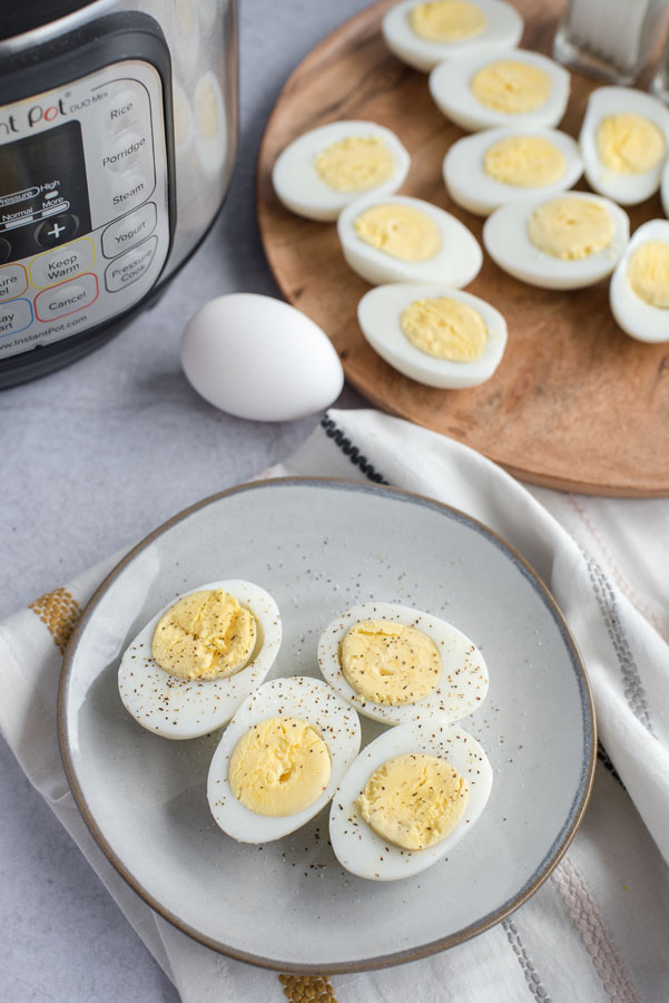 Overhead of a grey ceramic plate with four halves of perfectly cooked hard-boiled eggs with black pepper on a grey slate background with an Instant Pot and tray of more eggs in the background.