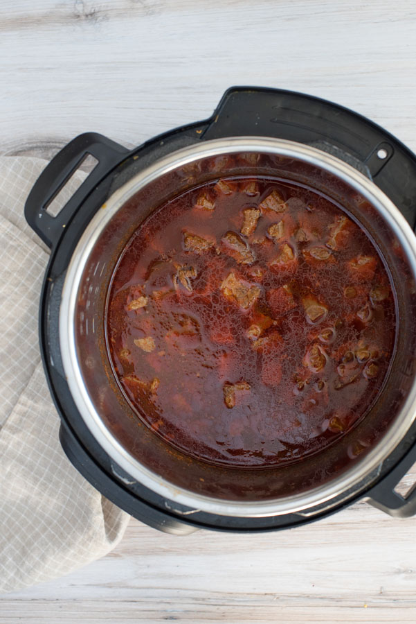 Overhead of an Instant Pot with red Colorado Chile made from cubed beef rump roast, enchilada sauce and beef bouillion.