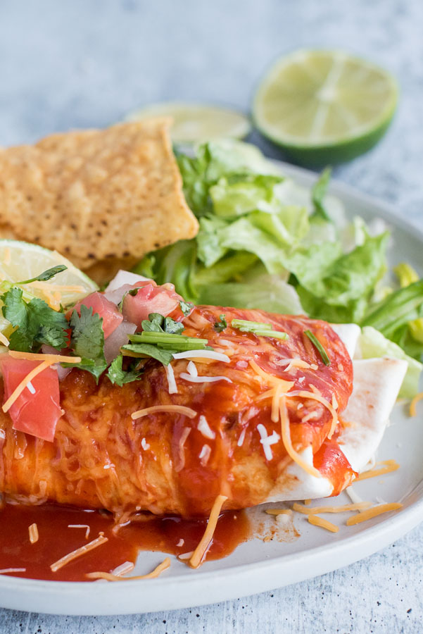 Close up on a white dinner plate with a freshly made Instant Pot / Pressure Cooker Chile Colorado Burrito smothered in red enchilada sauce, melted Colby jack cheese, fresh salsa and lime, served with tortilla chips and romaine lettuce.