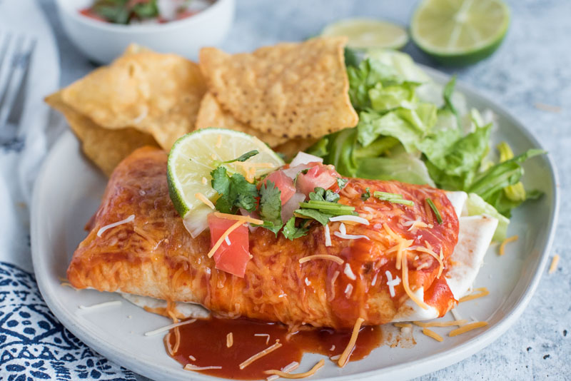 Close up on a white dinner plate with a freshly made Instant Pot / Pressure Cooker Chile Colorado Burrito smothered in red enchilada sauce, melted Colby jack cheese, fresh salsa, and lime, served with tortilla chips and romaine lettuce.