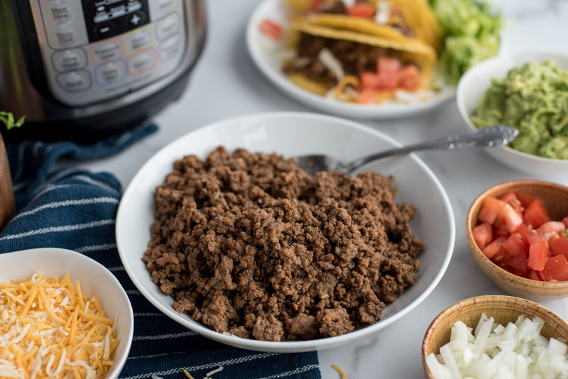 45 degree angle of ground beef in a bowl surrounded by bowls of guacamole, tomatoes, onions, and shredded cheese placed in front of an Instant Pot.