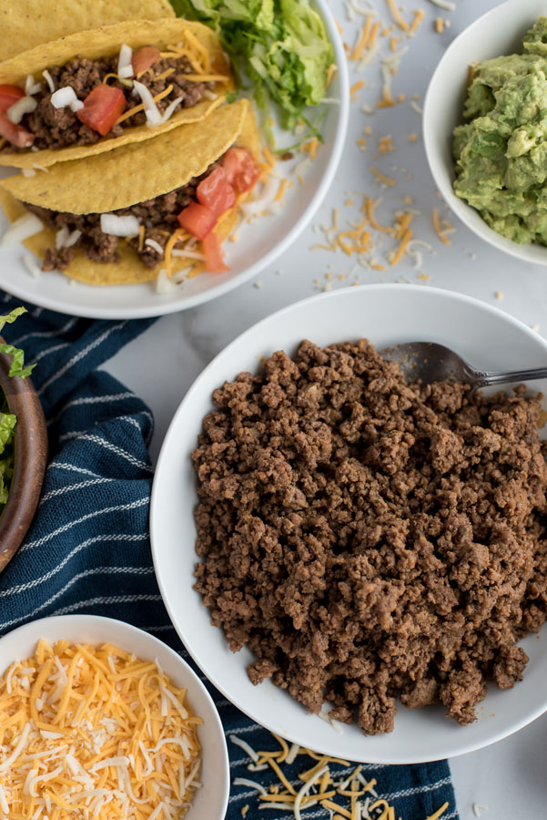 Overhead shot of ground beef taco meat made in and Instant Pot surrounded by a bowl of cheese and guacamole with prepared tacos on a plate.