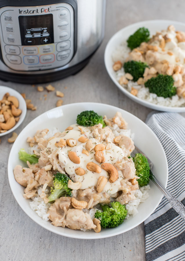 Overhead shot of a rosemary cashew chicken in a bowl with rice, cashews, and broccoli. Set in front of an Instant Pot.