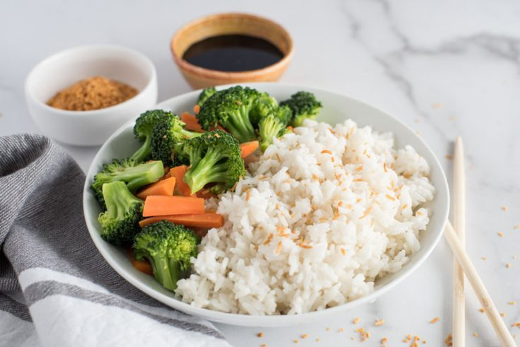 Large wooden dish filled with instant Pot coconut rice topped with toasted coconut flakes and served with steamed green broccoli florets, orange carrot sticks on a white and grey marble background next to a pair of wooden chopsticks