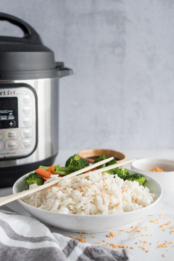 Side view of a white bowl of instant pot coconut rice topped with toasted coconut flakes next to steamed broccoli and carrots on a white and grey background in front of an instant pot pressure cooker