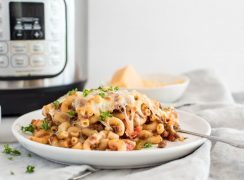 Instant pot american chop suey / beefaroni in front of an electric pressure cooker, with ground beef and mozarella cheese