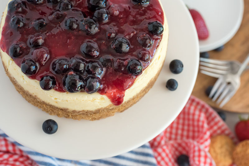 Close up overhead shot of Instant Pot cheesecake topped with berry topping and placed on a white cake stand with red, white, and blue napkins in the background.