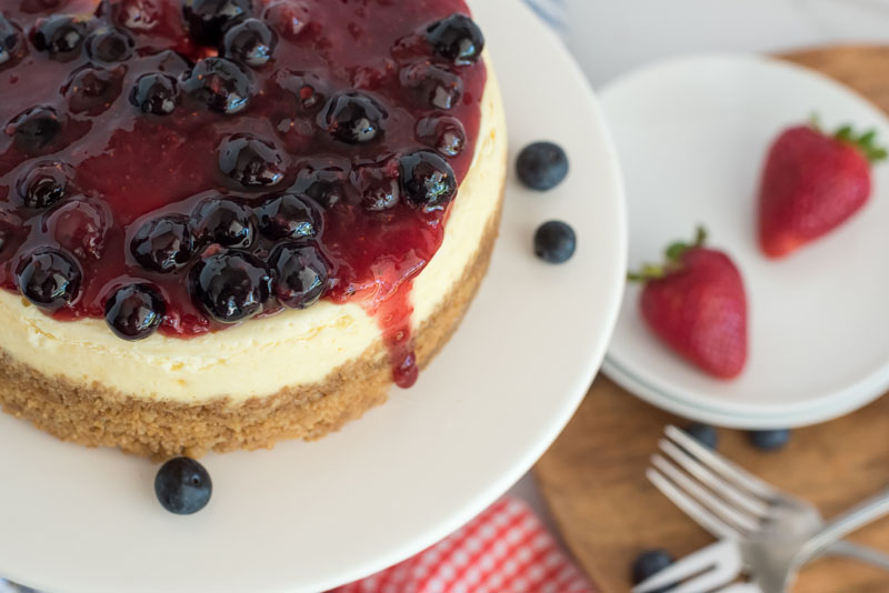 Close-up shot of the Red White and Blue Instant Pot Cheesecake recipe. The cheesecake is positioned in the top corner, covered with dark red strawberry-blueberry compote, with a drip falling down the side. Fresh blueberries and strawberries are sprinkled to the side of the platter and an extra plate