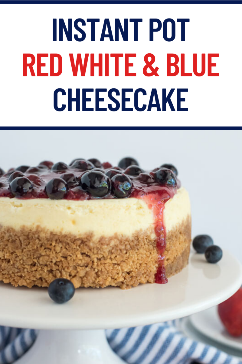 Instant Pot red white and blue cheesecake on a white cake stand with blueberries.