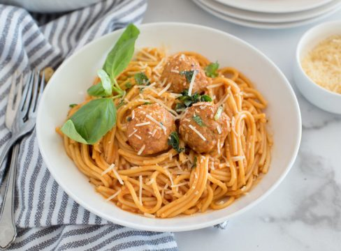 Close up on a white pasta bowl filled with instant pot spaghetti and meatballs made with frozen meatballs, spaghetti sauce and fresh basil leaves