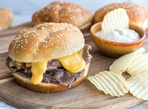 Instant pot beef and cheddar sandwiches on an onion roll with ruffle cut potato chips on a wooden cutting board