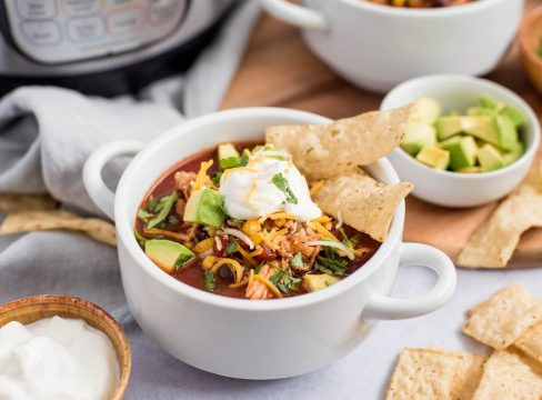 Close up picture of chicken enchilada soup topped with cheese, avocado, sour cream and chips. Placed in front of an Instant Pot.