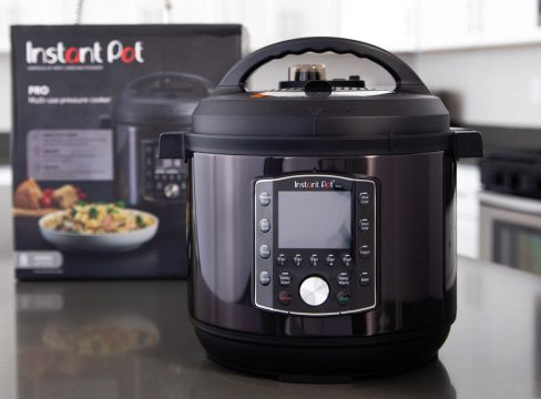 An Instant Pot Pro in black stainless steel sitting in front of the black Instant Pot box it came in